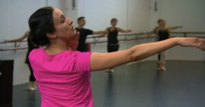 Female adult ballet teacher demonstrating extending her arm to the side to her adult ballet students in teh studio