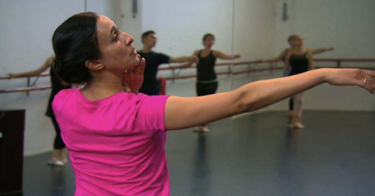 Ballet teacher in pink shirt looking along extended arm