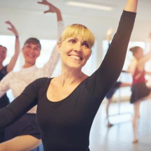 Senior female adult ballet dancer smiling at the barre.